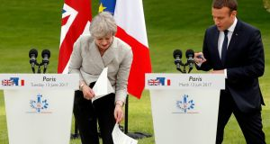Strong and stable? Theresa May's notes try to escape during her joint statement with Emmanuel Macron at the Élysée Palace in Paris. (Photograph: Reuters/Philippe Wojazer)