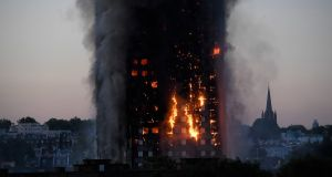 Flames and smoke billow as firefighters deal with the fire in a tower block at Latimer Road in West London.  Photo:Toby Melville / Reuters