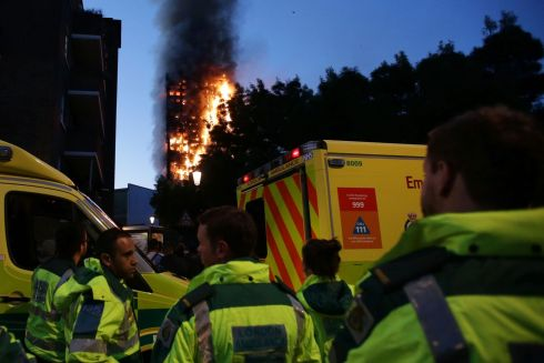 Members of the emergency services watch as Grenfell Tower is engulfed by fire. Photograph; AFP/Getty Images