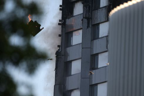 An arm holding a cloth can be seen waving from a window of Grenfell Tower as a piece of burning debris falls. Photograph: Getty Images