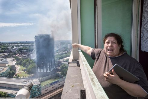 Local resident Georgina (no surname given) stands distraught on her balcony after a fire engulfed the 24-storey Grenfell Tower in west London.  Photograph: Rick Findler/PA