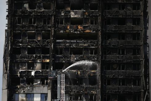 Hosing down Grenfell Tower as firefighters attempt to control the blaze. Photograph: Daniel Leal-Olivas / AFP