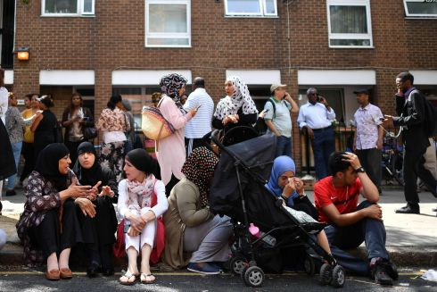 People affected by the fire that ripped through Grenfell Tower, a residential block sit on the pavement outside a temporary aid centre in west London.  Photograph:  Ben Stansallben  / AFP