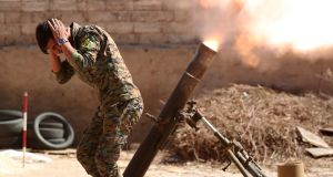A Kurdish fighter from the People's Protection Units (YPG) fires a 120mm mortar round in Raqqa, Syria. Photograph: Goran Tomasevic/Reuters