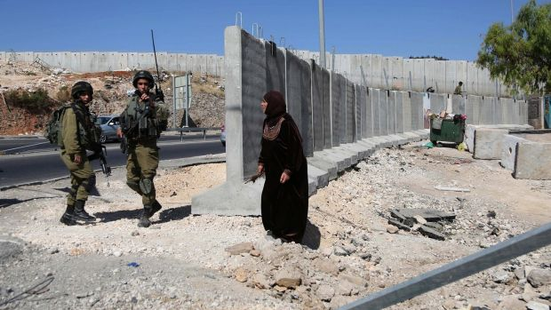 A Palestinian woman talks with Israeli soldiers as Israeli security forces in the  Hizma district of Jerusalem. Photograph:  Issam Rimawi/Anadolu Agency/Getty Images)