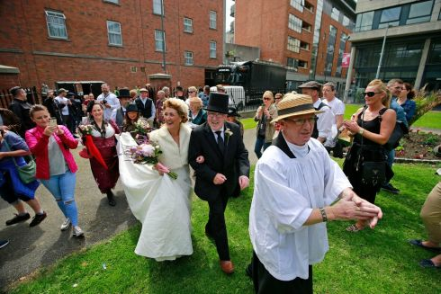 "Scene from ""Bloomsday In The Monto"",  including a mock wedding, organised by the North Inner City Folklore Project at Liberty House Park on Foley Street, Dublin 1. Priest played by Joe Dowling leading the Bride and Groom Councillor Christy Burke and Connie Murphy through the park Photograph: Nick Bradshaw / The Irish Times"