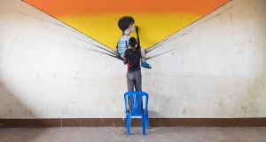 John (12), a refugee  from South Sudan, works on an art project at  Bidi Bidi. Photograph: Oscar Durrand