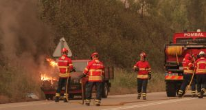 Firefighters try to extinguish a vehicle on fire  in Portugal. Photograph: EPA