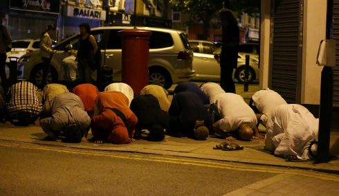 MUSTLIMS TARGETED: Muslims pray on a footpath in the Finsbury Park area of north London after a vehicle was driven into a group of pedestrians. Muslim leaders said worshippers were mown down after leaving the nearby mosque. Photograph: Daniel Leal-Olivas/AFP/Getty Images