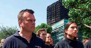Members of London's emergency services observe a minute's silence in memory of the victims of last week's fire at the Grenfell Tower block, in Kensington, west London. Photograph: Niklas Halle'n/AFP/Getty Images