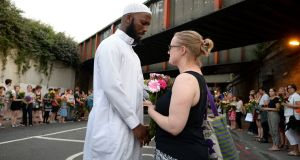 A Christian women gives a Muslim man flowers as they gather close to Finsbury Park mosque in north London, following a terror attack. Photograph: John Stillwell/PA Wire