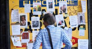 A man looks at a board showing pictures of the missing from the Grenfell Tower  fire  in north Kensington on Tuesday.  Photograph: Niklas Halle'n/AFP/Getty Images