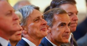 Philip Hammond, UK chancellor of the exchequer (centre left) and Mark Carney, governor of the Bank of England (centre right): Mr Hammond put protecting financial services ahead of controlling migration. Photograph: Luke MacGregor/Bloomberg