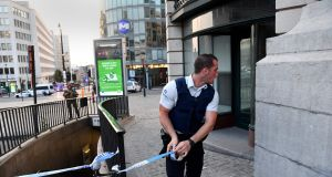A police official uses tape to cordon off an area outside Brussels Central Station, after an explosion in the Belgian capital. Photograph: Emmanuel Dunand/AFP/Getty Images