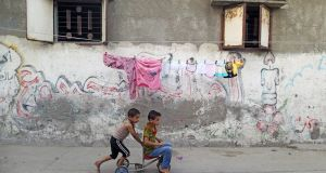 Palestinian children play outside their house at Shati refugee camp in Gaza City. Photograph: Mohammed Salem/Reuters