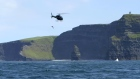 Divers jump from a helicopter near the Cliffs of Moher