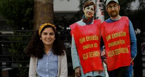 Esra Özakça poses with pictures of her husband, Semih, a primary school teacher, and university lecturer Nuriye Gülmen, who are both in prison and on hunger strike in Turkey. They were arrested after a prolonged protest over their dismissals in the crackdown that followed last July's attempted  coup. Photograph: Umit Bektas/Reuters