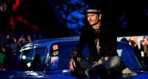 Actor Johnny Depp poses on a Cadillac before presenting his film 'The Libertine', at Cinemageddon at Worthy Farm in Somerset during the Glastonbury Festival. Photograph: Reuters/Dylan Martinez
