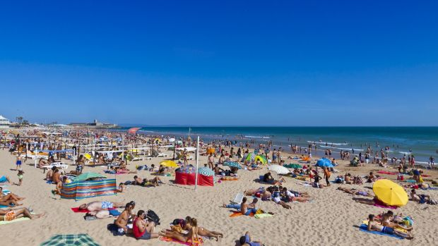 Lazy days: People sunbathing at the beach in Carcavelos town, near Lisbon. Photograph: iStock/Getty Images