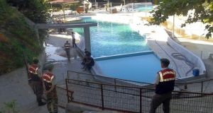 Paramilitary police officers investigate after five people were caught up in an electrical current in the pool at the park in  Akyazi, in Sakarya province, western Turkey. Photograph: IHA via AP