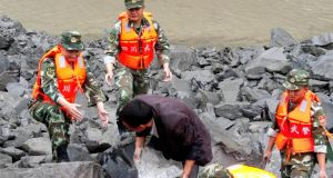 China landslide: military police and rescue workers lift rocks in Xinmo village. Photograph: AFP/Getty