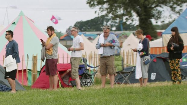 Glastonbury: the former shadow chancellor Ed Balls (third right) and his wife, Yvette Cooper (second right), queue for the showers at Worthy Farm. Photograph: Yui Mok/PA Wire