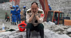 A rescue worker takes a nap at the site of a landslide in Xinmo village in Maoxian County in southwestern China's Sichuan Province. Photograph: AP