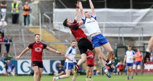 Down's Conor Maginn and Kieran Hughes of Monaghan contest a high ball at the Athletic Grounds. Photograph: Philip Magowan/Inpho