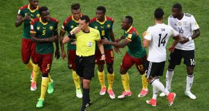 Cameroon players argue with referee Wilmar Roldan after he sent off the wrong player. Photo: Buda Mendes/Getty Images
