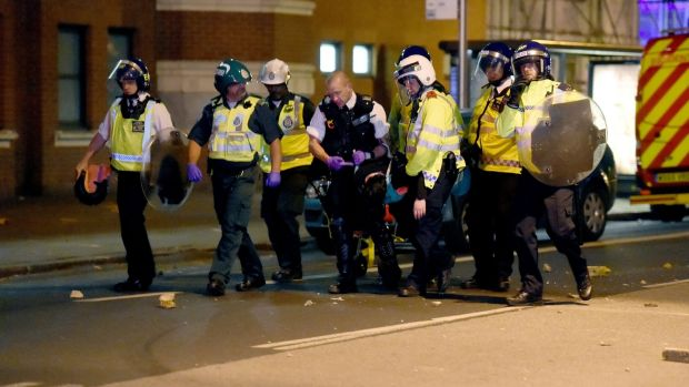 Police officers hold a person on Romford Road in Forest Gate, east London, during clashes on Sunday night. Photograph: PA