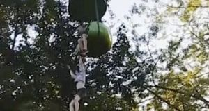 A 14-year-old girl is seen hanging from an amusement park ride in New York, seconds before she fell, to be caught by bystanders. Image: Still from  video by Leeann Winchell