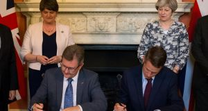 Britain's  prime minister Theresa May (right) stands next to Democratic Unionist Party (DUP) leader Arlene Foster (left), as DUP MP Jeffrey Donaldson (second left) sits and signs paperwork with Britain's parliamentary secretary to the Treasury, and chief whip, Gavin Williamson, whilst posing for a photograph inside 10 Downing Street on Monday. Photograph: Reuters