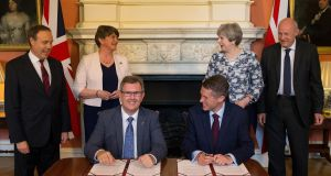 British prime minister Theresa May stands next to Democratic Unionist Party (DUP) leader Arlene Foster, as DUP MP Jeffrey Donaldson signs paperwork with the London government's chief whip, Gavin Williamson, inside 10 Downing Street. Photograph: Daniel Leal-Olivas/Reuters