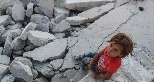 A child sits among the rubble of houses destoyed in air strikes during Eid al-Fitr in Al-Nashabiyah, Syria. Photograph: Mohammed Badra/EPA