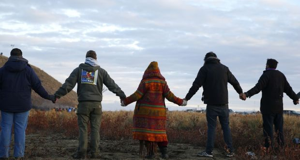 Protestors join hands in prayer as police line the hill at Standing Rock in  North Dakota a6cd78ad8a2c