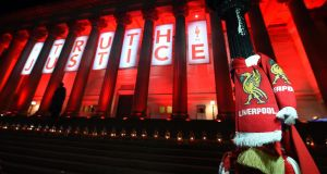 Liverpool scarves hang on a lamp post as St George's Hall is lit up in red with a giant banner reading 'Truth' and 'Justice' in April 2016. Photograph: EPA