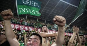 Fans of Beijing Guoan display a 'Green Invasion' flag during a match against Chongcing Lifan FC in 2015. Photograph: Kevin Frayer/Getty Images
