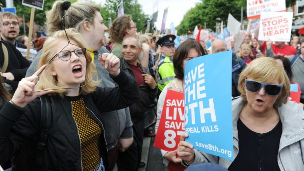 An anti-abortion demonstrator passes a pro-choice protester holding a coat hanger to her face during the march in Dublin. Photograph: Aidan Crawley