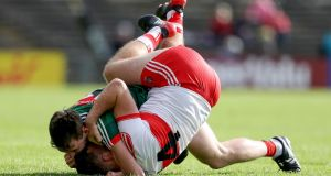 Mayo's Diarmuid O'Connor with Emmett McGuckin of Derryget to grips with each other. Photograph: Tommy Dickson/Inpho