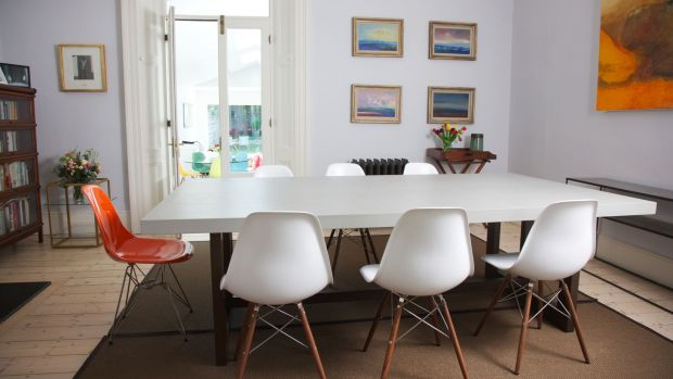 Interconnecting with the living room a set of French doors lead down into the large open plan kitchen. Eames-style chairs in white and orange surround an antique dining table. Photograph: Emily Quinn