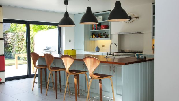 The painted in-frame kitchen features pendant lighting from Industry, a fruit bowl by Universal Positivo, a George Nelson-style clock, and barstools that are replicas of the Norman Cherner classic. Photograph: Emily Quinn
