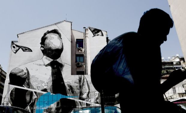 A man walks past a wall mural by the artist INO in Athens. Photo: Kostas Tsironis/Bloomberg