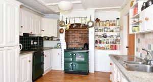 The  kitchen/diningroom has a green Stanley range in a brick-lined alcove.
