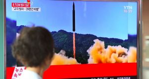 A woman walks past a television screen showing a picture of North Korea's launch of an intercontinental ballistic missile (ICBM), at a railway station in Seoul on July 4, 2017. Photograph: Jung  Yeon-Je/AFP/Getty Images