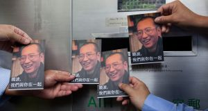Chinese activists hold some of the one thousand postcards containing messages of support to be sent from the public to Liu Xiaobo. Photograph: Alex Hofford/EPA