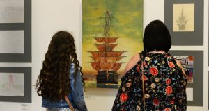 Emma and Anita Curry from East Wall admiring a tall ship painting by Dympna O Halloran. Photograph: Cyril Byrne/The Irish Times