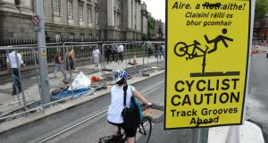 "Warning sign at  Luas track at College Green: In January, a cyclist whose wheel got caught close to the Spire said, ""My head took all the impact and if I wasn't wearing a helmet my head would have been split open like a melon."" Photograph: Dara Mac Dónaill"