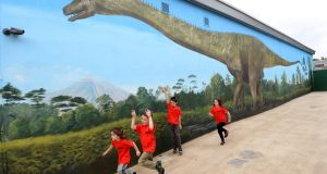 Alfie and Maisie Conroy, Raheny and Senan and Rian Shah, Greenwood, run past a mural of a Diplodocus in Dublin Zoo at the official opening of Zoorassic World. Photograph: Dara Mac Dónaill