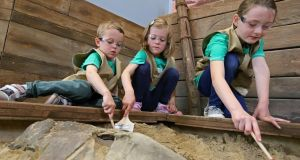 Jodie Hand (9) from Rathfarnham, Sophia Tennant (5) and Andrew Tennant (3) of Drumcondra dig for fossils at Dinosaur Discovery pictured this morning at the official opening of Zoorassic World at Dublin Zoo. Photograph: Colin Keegan, Collins Dublin