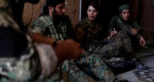 Kurdish fighters from the People's Protection Units (YPG) sit in a house in Raqqa, Syria. Photograph: Goran Tomasevic/Reuters